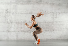 Side View Of Muscular Focused Brunette With Ponytail And In Sportswear Jumping In Front Of Brick Wall In Gym.