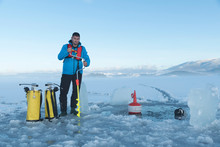 Young Caucasian Man Making Hole In A Frozen Lake For Ice Diving. Selective Focus