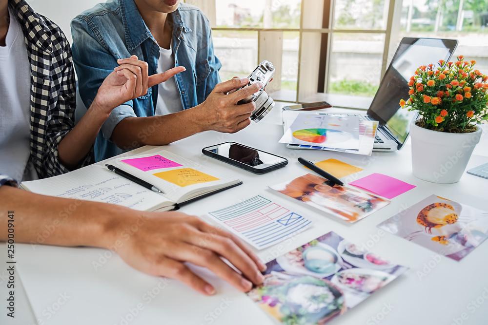 Fototapeta Asian advertising designer creative start-up team discussing ideas in office.