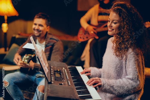 Woman playing clavier. Selective focus on woman. Home studio interior. - 250011179