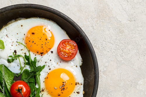 Fototapeta Border with fried eggs with herbs and cherry tomatoes on pan obraz