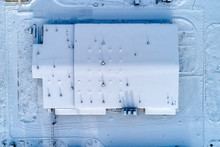 Large Warehouse Complex, The Roof Of The Building Is Completely Covered With Snow.