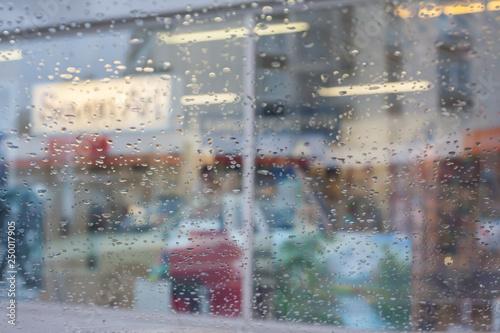 Türaufkleber London roten bus Rain drops on car glass, focus on raindrops. View to the street.