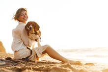 Image Of Positive Woman 20s Hugging Her Dog, While Sitting On Sand By Seaside
