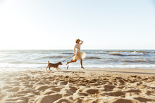 Image Of Beautiful Woman In Straw Hat, Running With Her Brown Dog Along The Coast