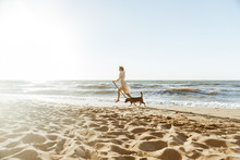 Image Of Happy Woman In Straw Hat, Running With Her Brown Dog Along The Coast
