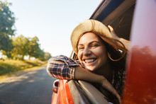 Image Of Joyous Woman 20s Wearing Straw Hat Smiling And Looking Out Of The Window, While Riding In Car