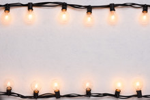 Garlands Of Glowing Warm Lamps On White Painted Wall