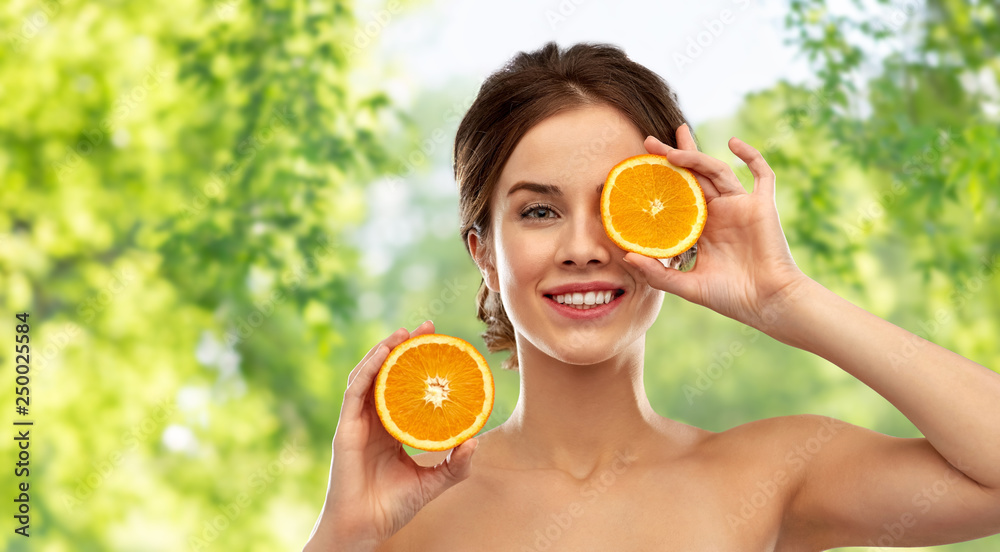 Fototapeta beauty and people concept - smiling young woman with oranges over green natural background