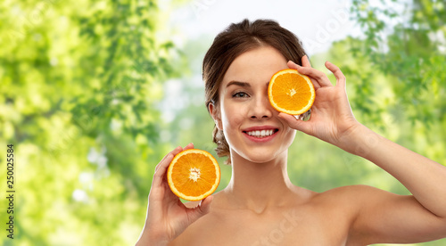beauty and people concept - smiling young woman with oranges over green natural Obraz na płótnie