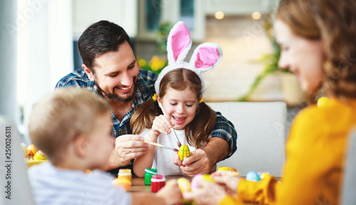 Happy easter! family mother, father and children paint eggs for holiday Canvas Print
