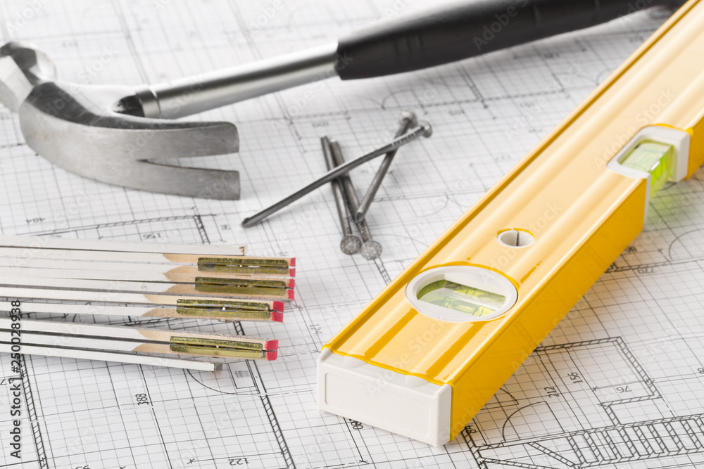 Fototapeta Construction tools  with hammer, nails, folding rule and level on architectural blueprint plan
