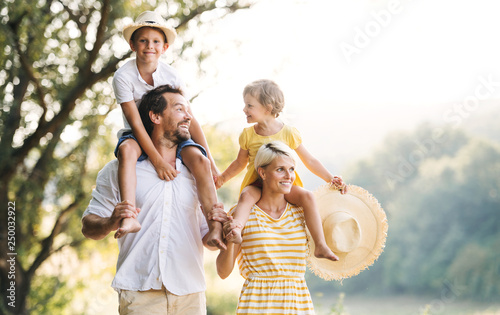 Obraz Young family with small children in sunny summer nature. - fototapety do salonu