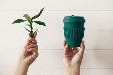 Hands holding stylish reusable eco coffee cup and green bamboo leaves on white wooden background. Zero waste. Green Cup from natural bamboo fiber. Ban single use plastic. Make a choice