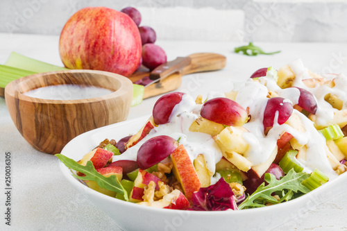 Obraz na plátně Waldorf salad with apples, celery, grapes, walnuts and arugula on white plate