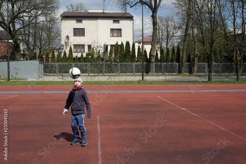 Fototapeta chłopiec kopie piłkę  obraz