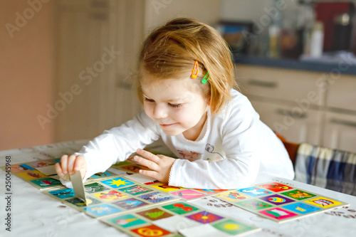 Foto Adorable cute toddler girl playing picture card game at home or nursery