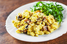 Scrambled Eggs With Mushrooms And Arugula Salad In White Plate On Wooden Table Background