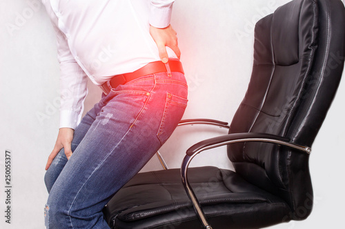 Photo A man in the office holding his back from a chair, the concept of back pain, int