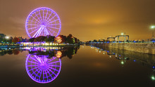 A Large Ferris Wheel In Montreal Is Effectively Reflected In The Water. Night City