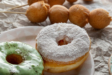 Two Donuts, One With Icing, The Second Is Sprinkled With Coconut Chips.