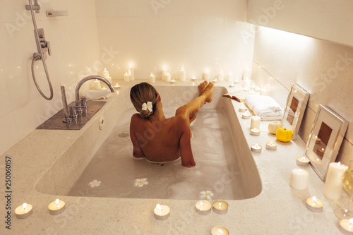 Canvas Woman relaxing in bath with candles