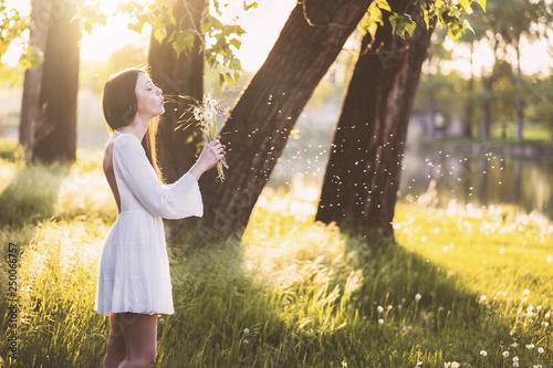 Montage in der Fensternische Lowenzahn Woman wearing a white dress blowing a dandelion