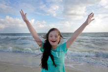 Portrait Of Down Syndrome Girl Smiling On Background Of The Sea