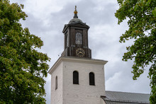 Old Church Tower Against A Gray Cloudy Sky