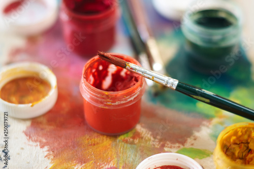 On the palette there are jars with gouache of different colors: red, Burgundy, y Fototapeta