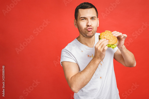 Fototapeta Funny hungry bearded man eating junk food. Excited young man greedily eating hamburgers isolated on red background. obraz