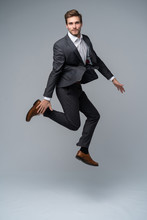 Mid-air Style. Handsome Young Man In Full Suit Jumping Against Gray Background.