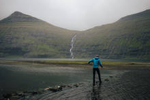Man Treading Carefully Over Stones In A River On Hike To Reach Waterfall In Faroe Islands