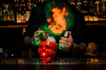 Bartender Spraying On The Cocktail In The Scull Cup From The Vaporizer In The Green Light And Fire It