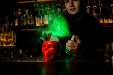 Bartender Spraying On The Cocktail In The Red Scull Cup From The Vaporizer In The Green Light