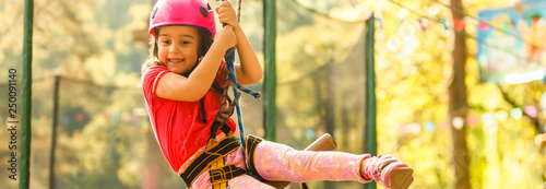 Little beautiful girl climbs on rope harness in summer city park. Canvas Print