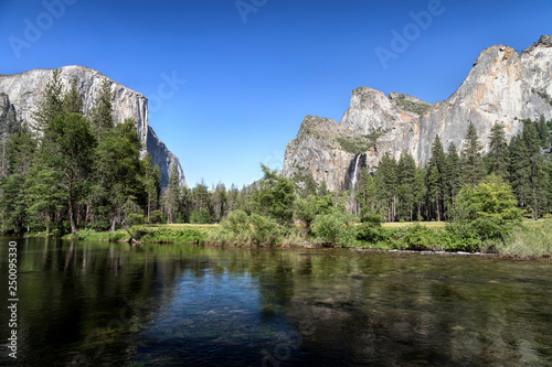 Photo  Iconic features of the amazingly beautiful Yosemite Valley are viewed from the bank of California's Merced River