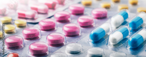 Heap of medical pills in white, blue and other colors. Pills in plastic package. Panoramic banner for design.