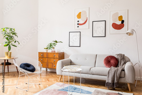 Valokuvatapetti Stylish vintage decor in a spacious flat interior with design grey sofa, armchair, retro commode and posters on the wall