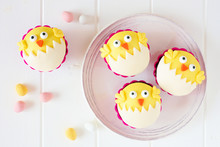 Hatching Spring Chick Cupcakes On A White Plate. Flay Lay Against A White Wood Background.