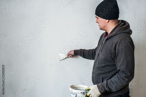 Fotografía  Man in a hat plastering the walls with finishing putty in the room with putty knife or spatula