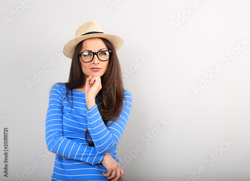 11d393e6d4 Happy thinking young woman looking up in fashion glasses and straw hat on  blue background