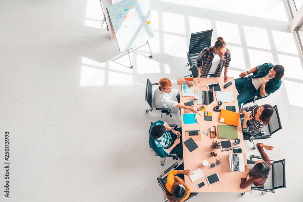 Fototapeta Multiethnic diverse group of business coworkers in team meeting discussion, top view modern office with copy space. Partnership professional teamwork, startup company, or project brainstorm concept