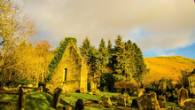 Landscape Of Ivy Covered Chapel Ruin In A Disused Rural Graveyard With Hills In The Background.