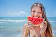 Portrait of beautiful girl with watermelon on the beach.