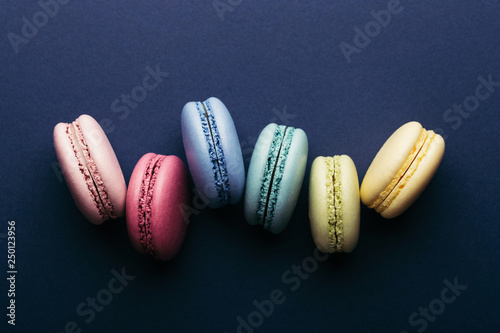 Colorful macarons on dark blue background. Top view. Tableau sur Toile