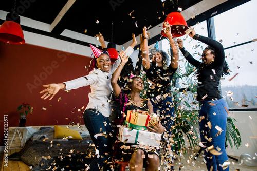 Staande foto Schilderingen Happy African American friends girls under falling confetti at the birthday party