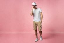 Full Length Of Attractive Confident Young Man In Hat Standing With Hands In Pockets Over Pink Background.