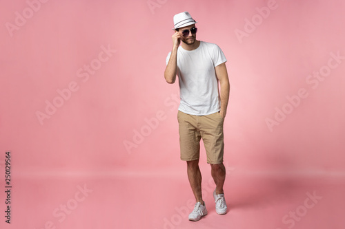Fotografía  Full length of attractive confident young man in hat standing with hands in pockets over pink background