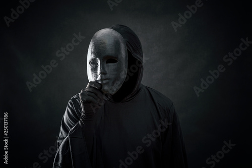 Scary figure in hooded cloak with mask in hand Canvas Print